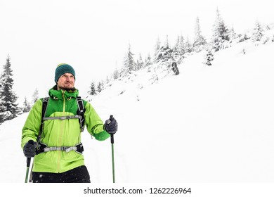 Winter trekking in white snowy forest, adventure concept. Man hiking in winter woods. Travel and healthy lifestyle outdoors in beautiful nature.