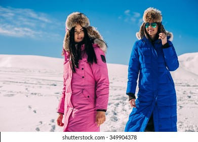 winter, two cheerful young girls having fun in the snow in the mountains