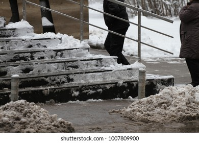 Winter. Uncleaned stairs. People walk on a very snowy stairs. People step on an icy stairs, slippery stairs. Dangerous uncleaned sidewalk