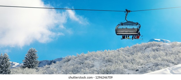winter vacation - chair lift above snowy mountain landscape at ski resort