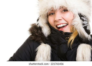 Winter vacation. Cheerful positive girl in warm clothes. Happy young woman in fur hat doing fun isolated on white.