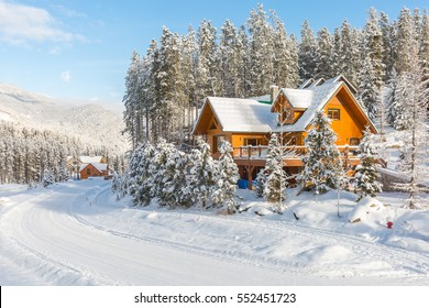 Winter vacation holiday wooden house in the mountains covered with snow and blue sky.