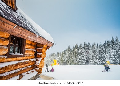 Winter vacation holiday wooden house in the mountains covered with snow. Pine trees forest and blue sky in the background. Active people with ski, snowboad. Sport, recreation. Bukovel resort, Ukraine