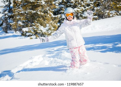 Winter vacation, ski - happy skier girl playing in snow