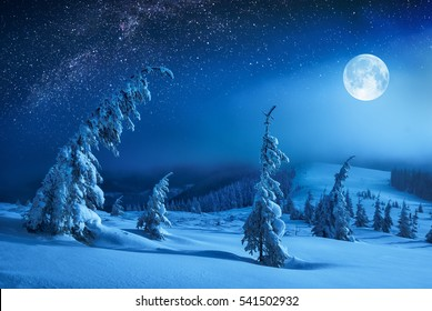 Winter valley covered with fresh snow in a light of rising moon. Fantastic milky way in a starry sky. Christmas night.