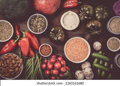 Winter vegetarian cooking ingredients,white wooden background, top view,with different vegetables and legumes