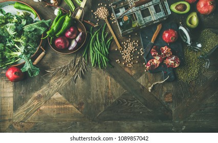 Winter vegetarian, vegan food cooking ingredients. Flat-lay of seasonal vegetables and fruits, beans, cereals, kitchen utencils, dried flowers, olive oil over wooden background, top view, copy space
