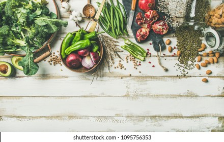 Winter vegetarian, vegan food cooking ingredients. Flat-lay of vegetables, fruit, beans, cereals, kitchen utencil, dried flowers, olive oil over white wooden background, top view, copy space