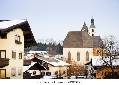 Winter view of buildings in Kitzbuhel ski resort with the Austrian Alps in the background.