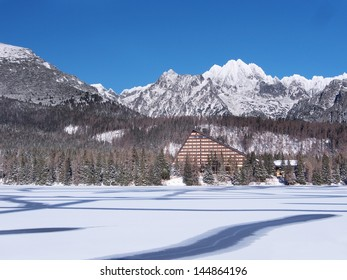 Winter view of frozen surface of Strbske Pleso (Tarn) with hotel and peaks of High Tatra mountains in background. Strbske Pleso is second largest glacial lake on the Slovak side of High Tatras.