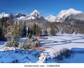 Winter view of frozen surface of Strbske Pleso (Tarn) and peaks High Tatra mountains in background. Strbske Pleso is second largest glacial lake on the Slovak side of the High Tatra Mountains.