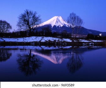 Winter view of Mount Fuji with mist and reflections in a lake