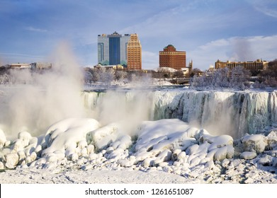 Winter view on Frozen Niagara American Falls waterfall with the skyline of Niagara Falls city, New York, USAб in the background seen from Canadian bank of Niagara river.