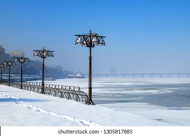 Winter view of the snow covered city on the river bank. Embankment with vintage metal lanterns and fence, Dnepropetrovsk, Dnipro city, Ukraine
