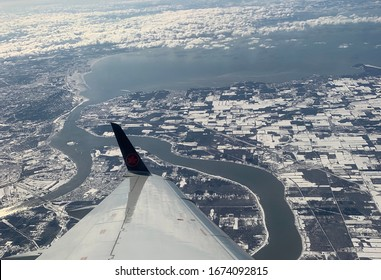 Winter view of Toronto, Ontario, Canada from an airplane. Plane landing with view of water and city from above.