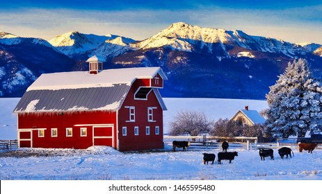Winter view of Wallowa Mountians and traditional red barn on cattle ranch near Joseph Oregon, USA