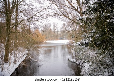 winter view of the white Vondelpark under the snow in Amsterdam  with a river and trees
