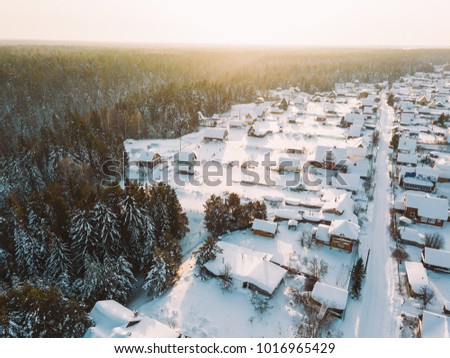 Winter village  landscape from aerial view. Houses in snow. Taiga forest. Siberia, Russia