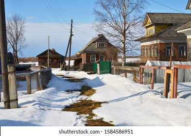 Winter in the village. Old Russian houses in the countryside. Snow melts on the road. Spring has come and the snow is melting in the village. Winter landscape of the village.