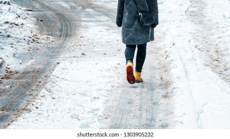 Winter Walk in Yellow Leather Boots. Back view on the feet of a women walking along the icy snowy pavement. Pair of shoe on icy road in winter. Abstract empty blank winter weather background