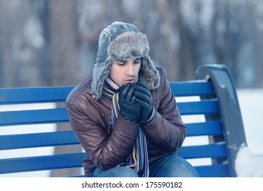 Winter walk - young man in an ear flap hat sitting on a bench and warming his hands