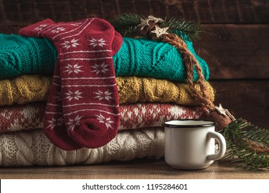 Winter, warm, knitted pullovers, Christmas socks and a mug of hot cocoa on a wooden background. Winter clothes. Ugly Christmas Sweater