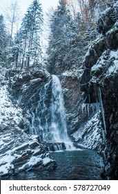 Winter waterfall in forest with icicles and snow