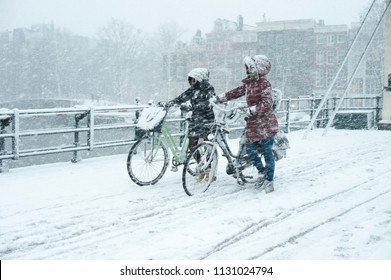 Winter weather, heavy snowfall in Amsterdam, Netherhands. Two people walking with bikes on a slippery road (Skinny Bridge/Magere Brug/Amstel).