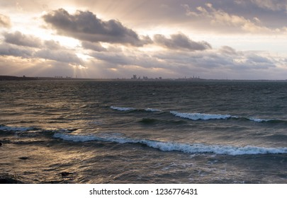 Winter Weather - Stormy sea and Dramatic Sky. City of Tallinn at the far horizon.