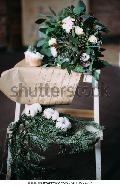 winter wedding decor: wedding bouquet, cupcakes, and spruce branches lie on a wooden stand