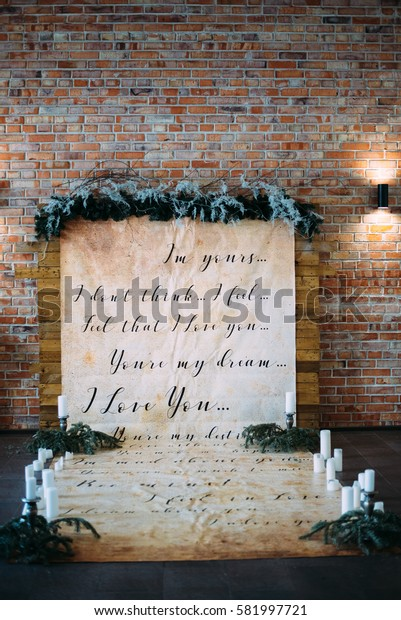 winter wedding decor and place for photography: brick wall, inscription about love, candlesticks, white candles, fir branches