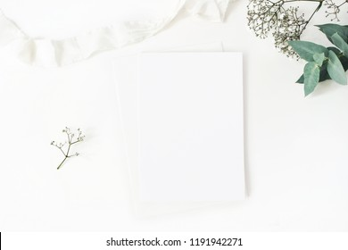 Winter wedding desktop stationery mockup. Blank greeting card, baby's breath Gypsophila flowers, eucalyptus branch and silk ribbon. White table background, top view. Christmas flatlay.