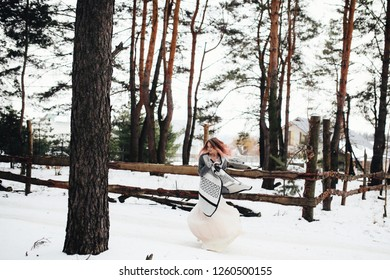 Winter wedding photo shooting. Charming bride with red hair walks across the forest in wedding dress and sweater