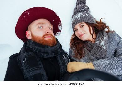 Winter weekend, couple in love having fun on snow in snowfall weather closeup