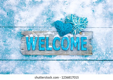 Winter welcome sign with rope hearts and snow hanging on antique teal blue wood door; seasonal background