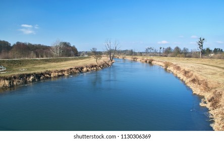 Winter wide river with blue water in open landscape with yellow grass