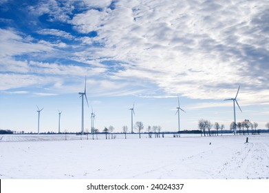 winter windmill park in a white snow landscape with blue sky and clouds