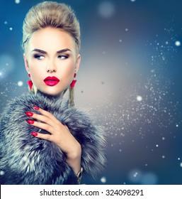 Winter Woman in Luxury Fur Coat. Beauty Fashion Model Girl in Blue Fox Fur Coat. Perfect Makeup and accessories. Beautiful Luxury Winter Lady