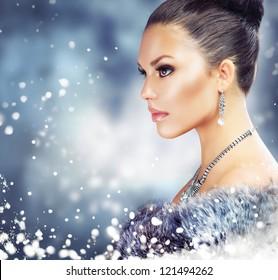 Winter Woman in Luxury Fur Coat.Beauty Christmas Girl Portrait. Fur Fashion. Snow. Jewelry