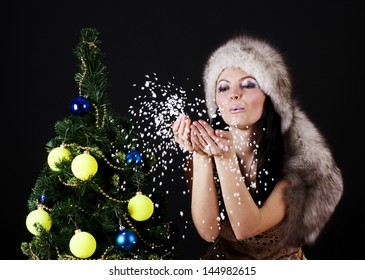 Winter woman near christmas tree blowing snow from hands, isolated on black.