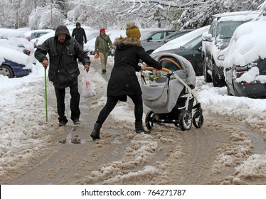 Winter. Woman push baby stroller through snow.  People are walking hard on a snowy icy road after a heavy snowfall in the city of Sofia, Bulgaria on Nov 28,2017, person with cane on an icy pathway.