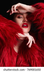 Winter Woman with red lips in Luxury Red Fur Coat. Beauty Fashion Model Girl portrait with perfect Makeup and clear skin. Beautiful glamour Luxury Winter Lady.