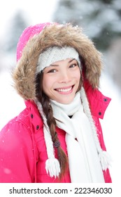Winter woman in snow outside in nature. Portrait closeup outdoors in snow. Happy beautiful smiling multicultural Asian Caucasian girl.