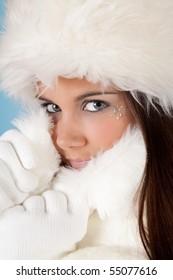Winter woman with white fur hat wearing warm woolen gloves
