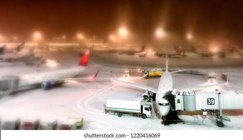 winter wonderland airport overview at night with snow aircraft apron passenger planes parked to terminal building gate aerial panoramic view air travel aviation transportation creative blur background