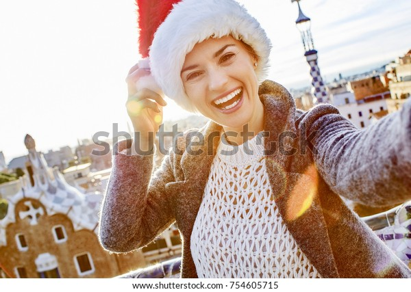 Winter wonderland in Barcelona at Christmas. smiling trendy traveller woman in a Santa hat at Guell Park in Barcelona, Spain taking selfie