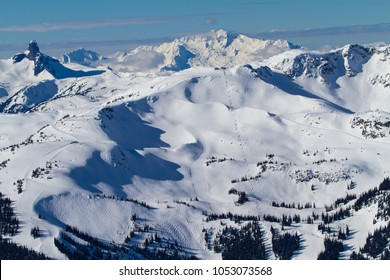 A winter wonderland scenic view of Whistler mountain and immense skiing terrain as well as showcasing beautiful scenery with Black Tusk and the Tantalus Range in the background