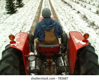 winter work - man driving tractor through the snow