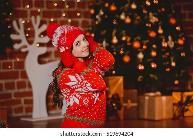 Winter, xmas portrait: Young woman dressed in red warm woolen cardigan, gloves and hat posing indoor near Christmas tree