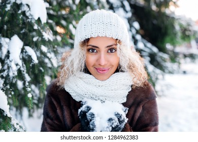Winter young woman blowing snow in snowy day in winter time at nature